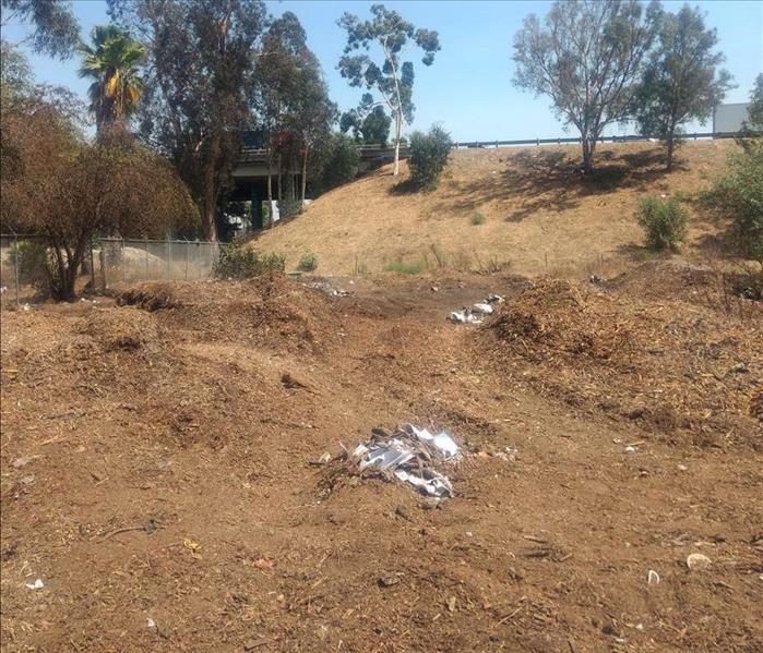 Dirt area next to freeway is now clear of any trash or debris