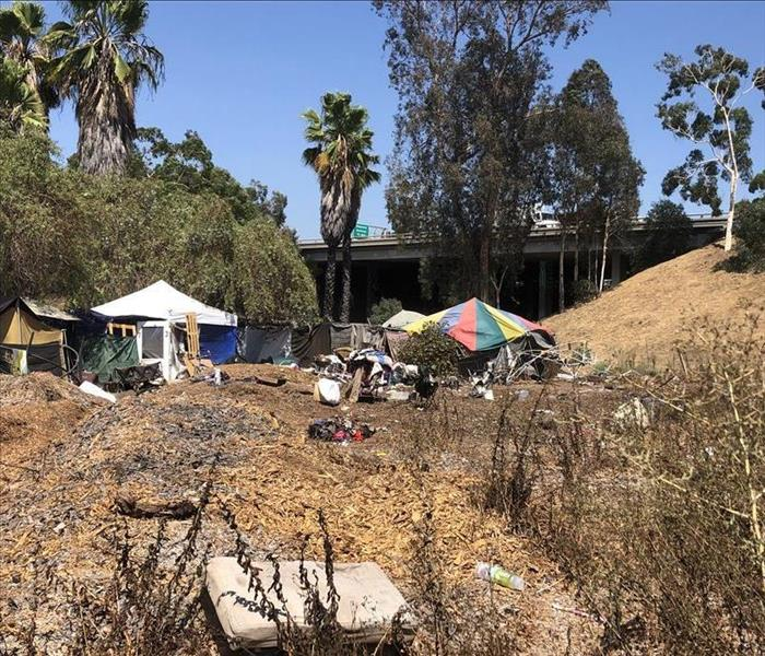 Homeless encampment in dirt area next to freeway