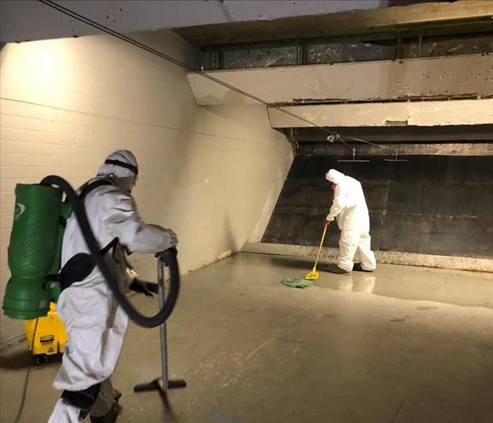 2 SERVPRO technicians mopping and vacuuming area where gravel was.