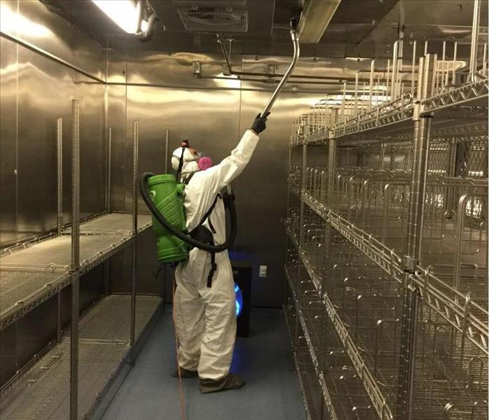 Servpro technician suited in ppe vacuuming in a silver supply room.