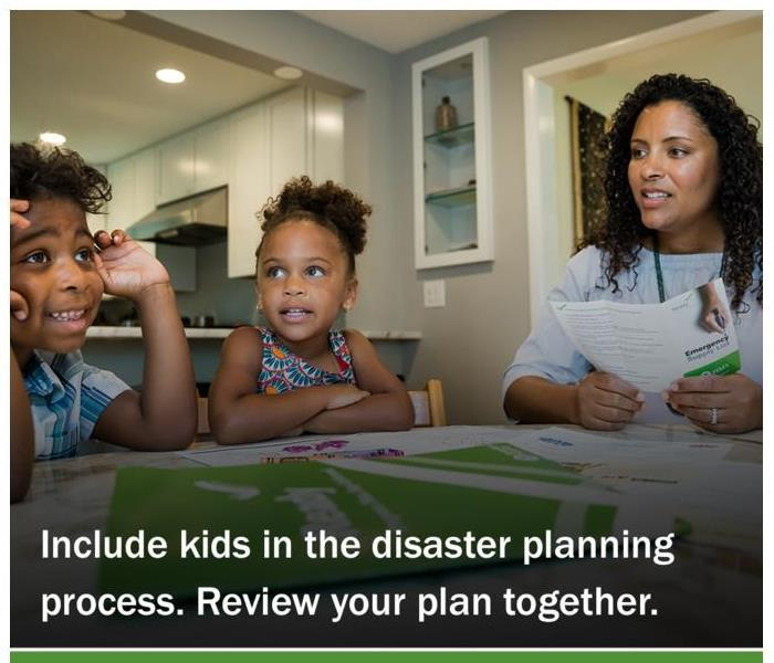 2 children and their mother sit around the kitchen table reviewing their disaster plan.